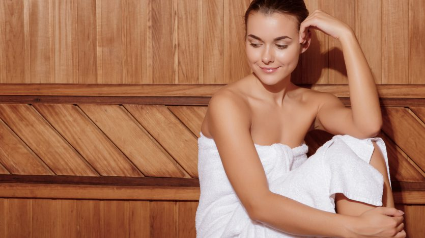 Spa procedures. Young dreamy woman relaxing in wooden sauna