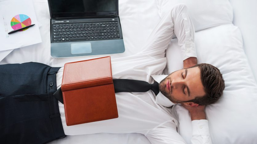 Businessman sleeping. Top view of handsome young man in shirt and tie holding hands behind head and keeping eyes closed while lying in bed at the hotel room